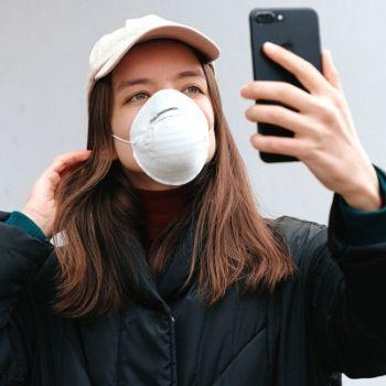 Woman wearing covid mask taking selfie